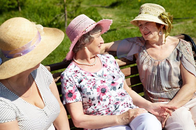 Independent supervised senior living residents socialize on a sunny park bench in FL