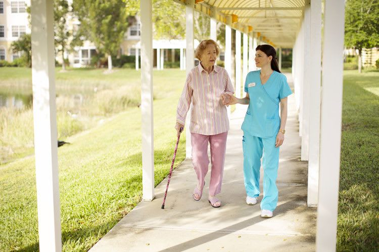 Assisted senior living nurse walks with a resident