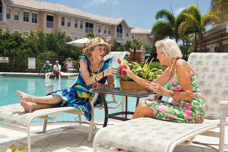 Senior living friends socialize by the pool