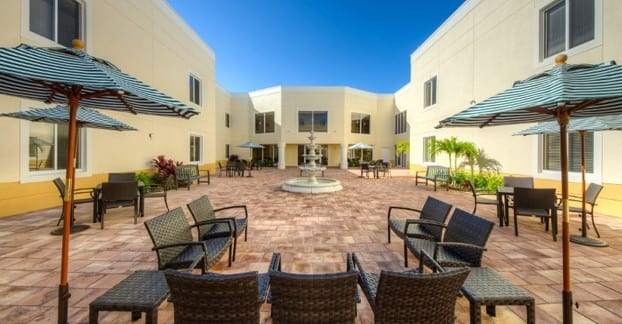 Florida senior living community features a sunny courtyard with a fountain and lounge chairs