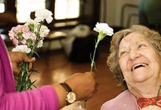 A  senior living resident receives a flower.