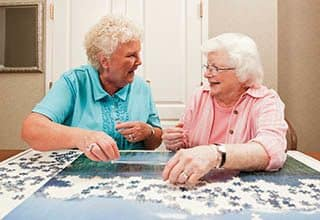 Senior living residents in Suwanee work on a puzzle.
