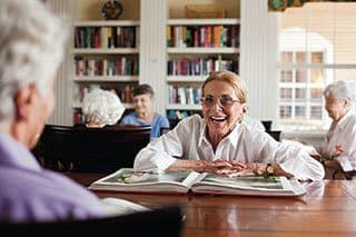 Senior living residents enjoying our private library collection in Naples