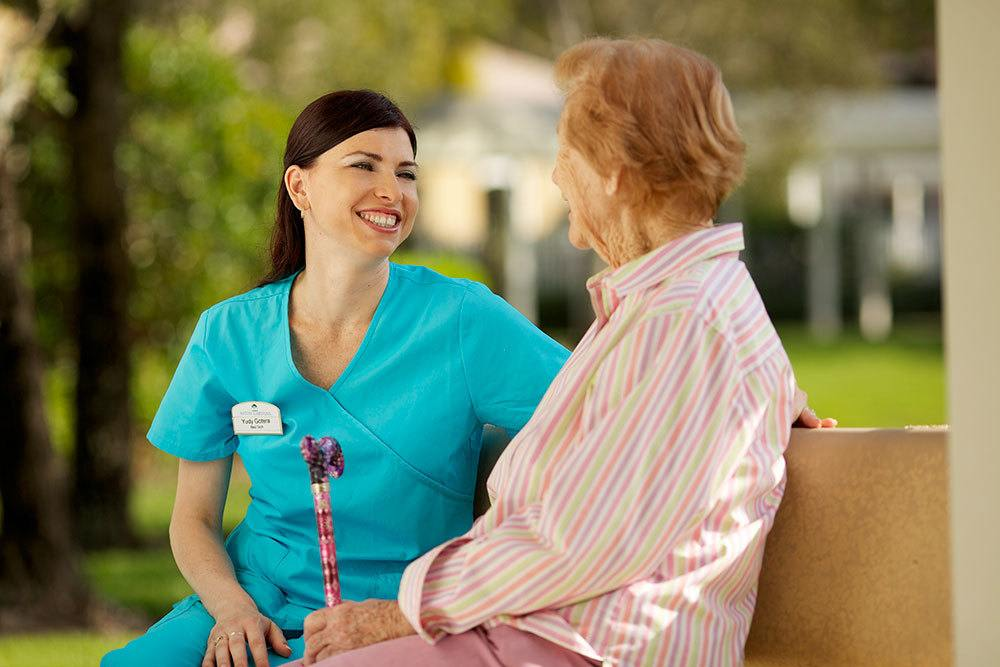 Senior living resident in Palm Beach Gardens sitting outside with a nurse