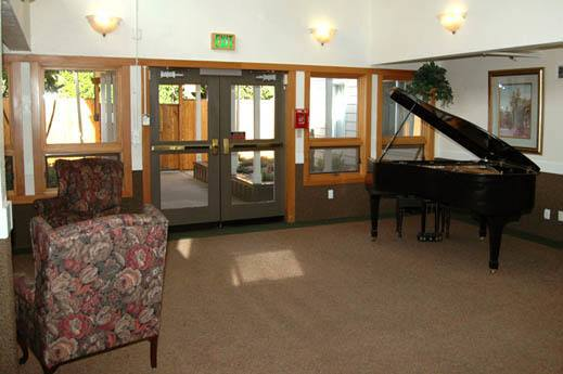 spacious lobby with piano inside SouthTowne Memory Care