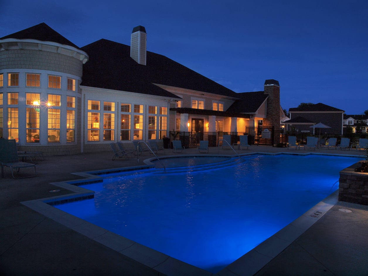 Clubhouse and pool lit up at night at Kendal on Taylorsville in Louisville, Kentucky
