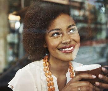 Woman smiling while drinking her coffee at Cameron Isles Apartments in Houma, LA.