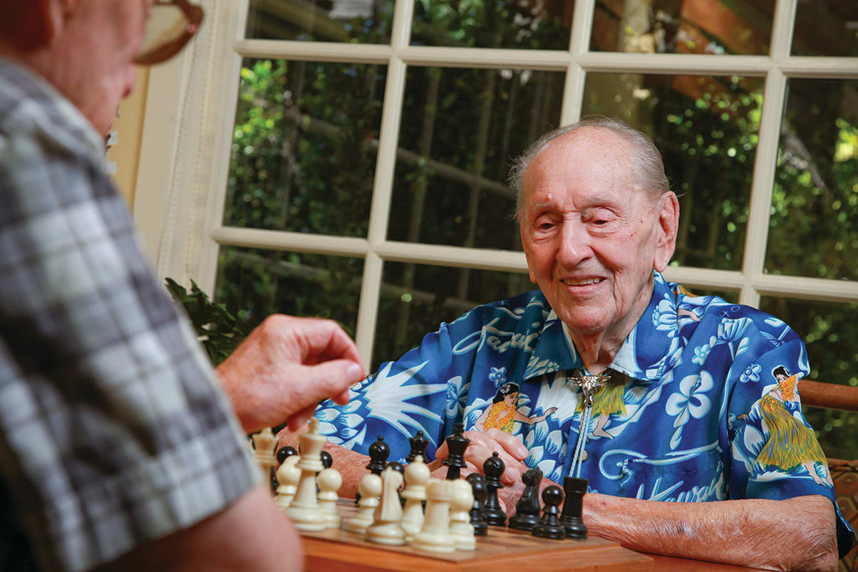 Senior men playing a round of chess at Cypress Court