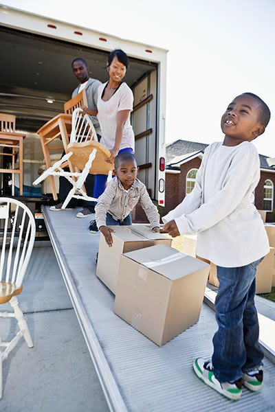 Picture of another happy family moving their items into the truck, almost ready to drive to their Magellan Storage facility!