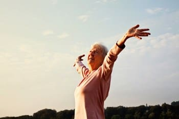Woman with her arms stretched out ot the sky in a field