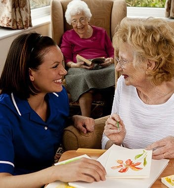 A CNA working with a resident on a piece of art at Addington Place of Johns Creek in Johns Creek, GA
