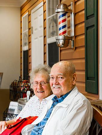 Senior couple sitting on bench smiling
