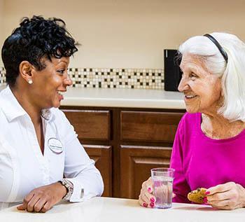 Senior woman and elderly care nurse talking