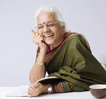 Lady sitting at table with a tea cup laughing
