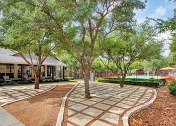 Apartment walkway with trees in San Antonio