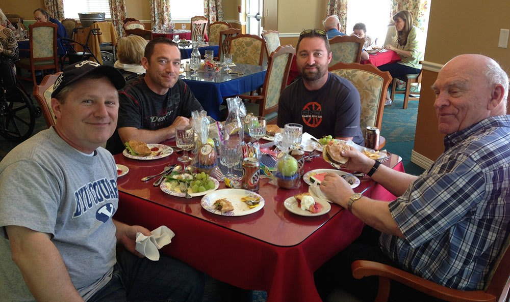 Resident eating food with family at the senior living community in Cedar Hills