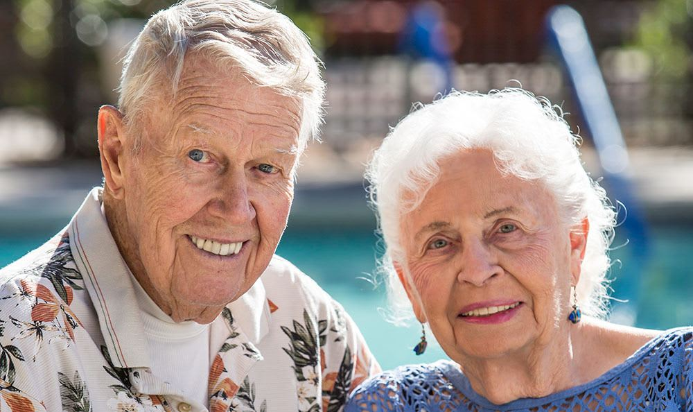 Couple by the pool at the senior living in Tucson