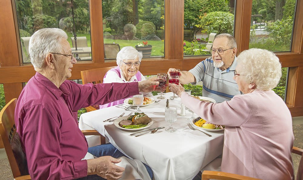 Friends enjoying food and drinks together at the senior living community in Olympia, WA