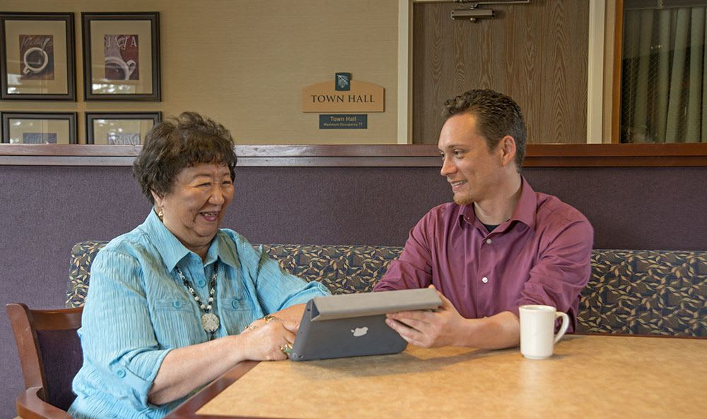 Resident spending time with a visitor and looking at an ipad at The Firs