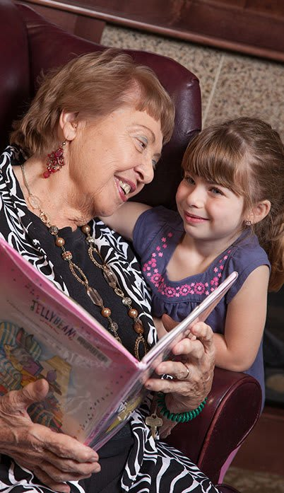 Resident reading a book to grandchild at the senior living community in Greenwood Village