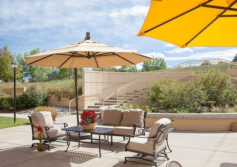 Umbrellas provide shade on the patio at the senior living community in Greenwood Village