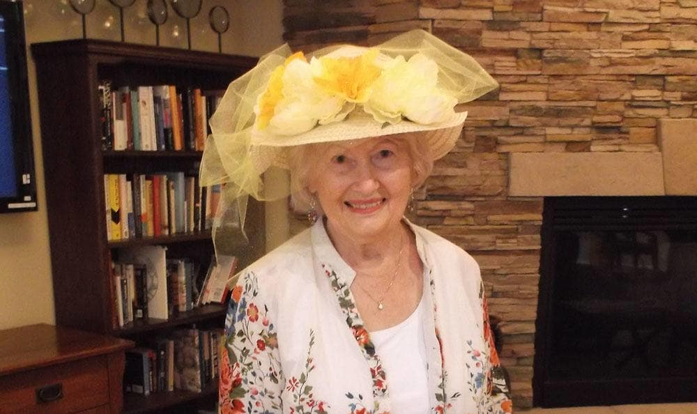 Resident poses in her Derby hat at the senior living community in Colorado Springs