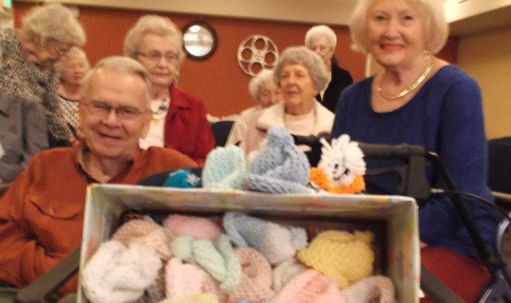 Residents show off knitted hats at the senior living community in Colorado Springs