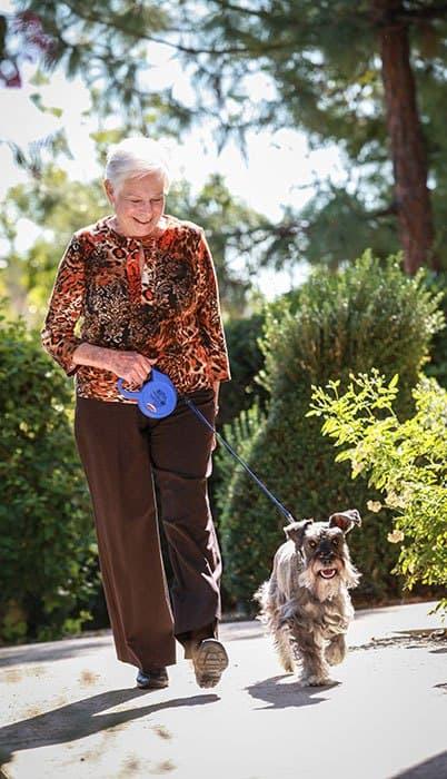 Resident walking her dog at the senior living community in Mercer Island