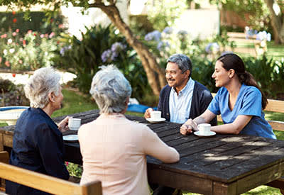 Residents drinking coffee outside at Cinco Ranch Alzheimer's Special Care Center in Katy, Texas.