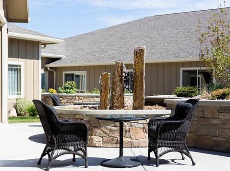 Outdoor patio lounge with a fountain at Cardinal Court Alzheimer's Special Care Center