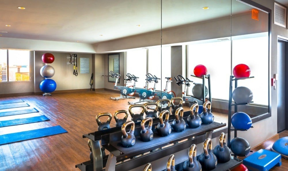 Yoga studio equipped with free weights and spin bikes