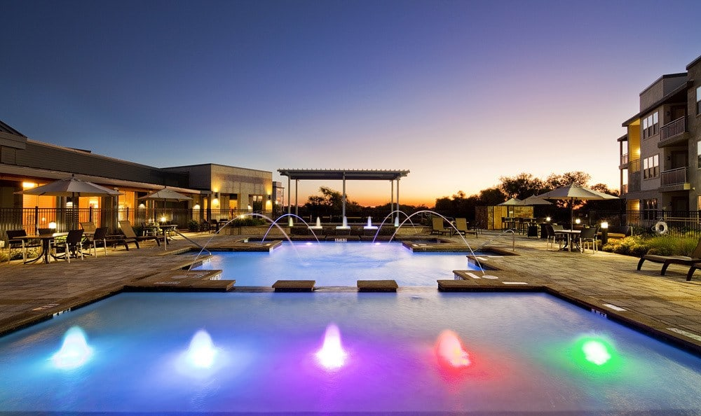 Pool with colorful fountains at The Landings at Brooks City Base.