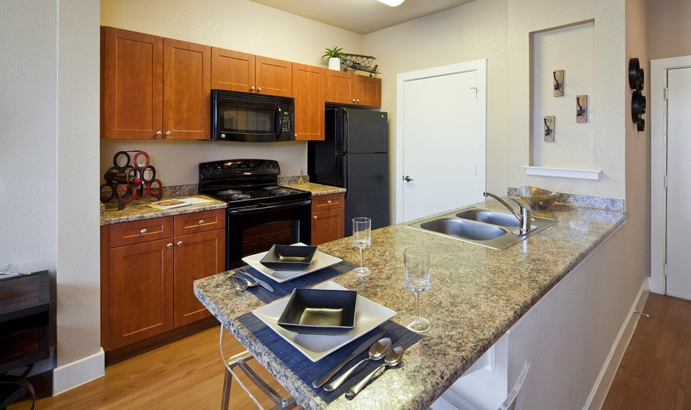 Standard kitchen with matching black appliances at The Landings at Brooks City Base.