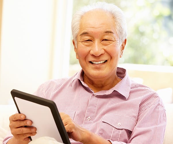 Senior man using a tablet to learn more about his retirement options via the Regency Pacific Management website.