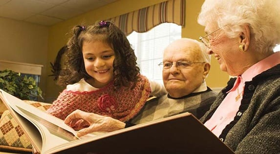 Seniors reading with their grandchildren at Regency Newcastle in Newcastle, WA