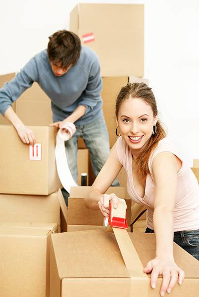 Man and woman taping boxes to move into American Mini Storage