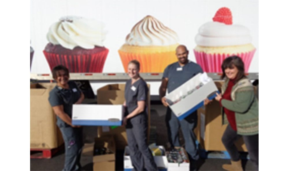 Employees at Animal Hospital of Lubbock moving supplies in front of a wall of cupcakes