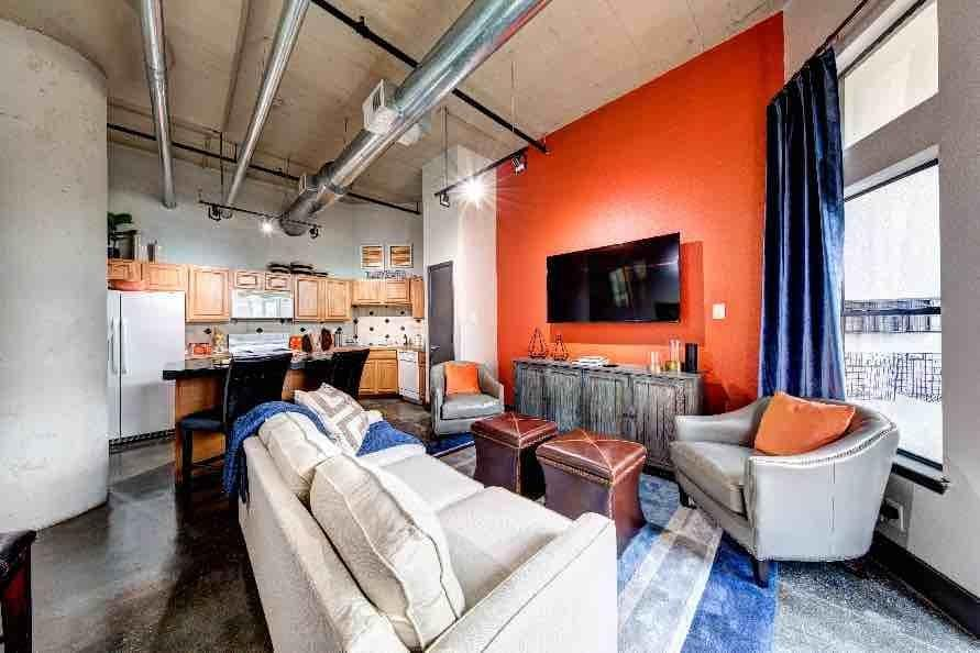 Enjoy company in the living room at The Marquis Downtown Houston Lofts in Houston, TX