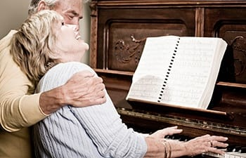 Jovial couple entertaining themselves with the piano at one of our AssistedSenior.com communities.