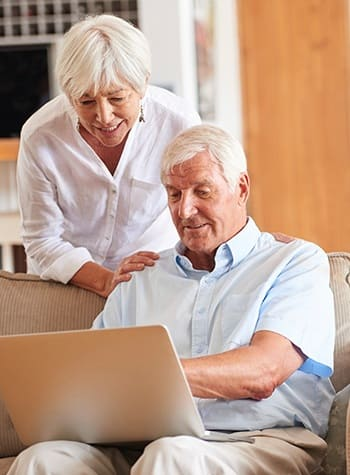 Couple considering their retirement options online - and looking into AssistedSenior.com communities