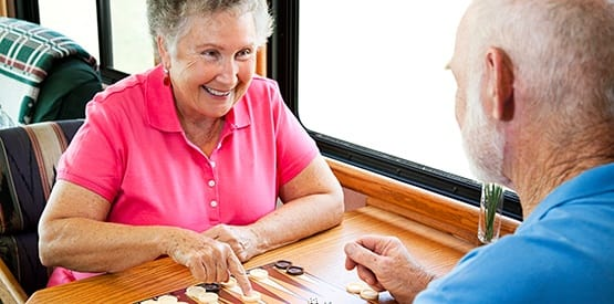 Couple enjoying a game of backgammon at one of our AssistedSenior.com communities