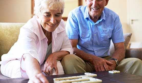 Happy couple at one of our AssistedSenior.com communities playing dominos