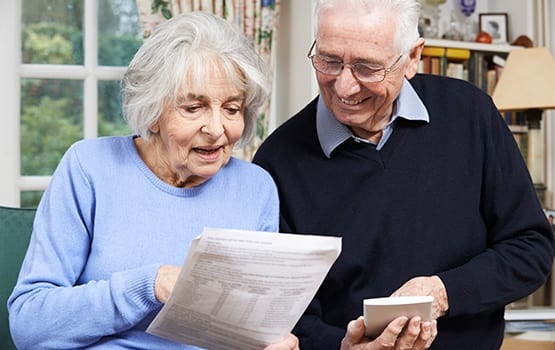 Senior couple reviewing their options regarding senior living communities, using the resources on Grand Villa of Delray West's website