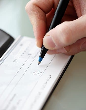 Caregiver writing a check for mom's stay at Grand Villa of Clearwater in Florida