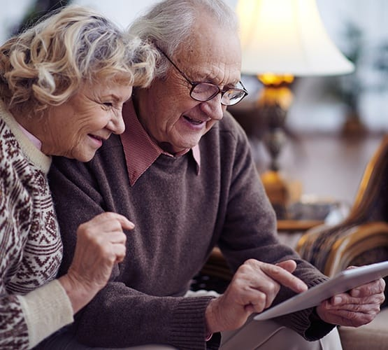 Senior couple looking at Grand Villa of Largo online in Florida