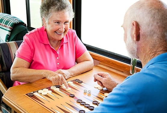 Another senior couple enjoying a game of dominos together during their Respite stay at our senior living community here at Grand Villa of Altamonte Springs in Florida