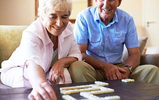 Senior couple having a ball playing backgammon as part of our Respite Care program here at Grand Villa of Pinellas Park in Florida