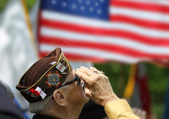 Proud senior citizen and Veteran saluting the flag. Senior veterans are welcome at our beautiful community here at Grand Villa of Deerfield Beach in Deerfield Beach