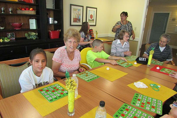 Residents enjoying Bingo with kids at Palmilla Senior Living