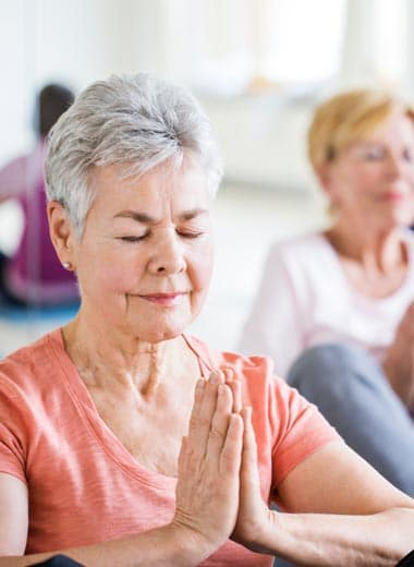 Woman participating in yoga class at Three Creeks Senior Living